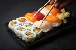 Hand using chopsticks pick Sushi and Sashimi rolls on a black stone slatter. Fresh made Sushi set with salmon, prawns, wasabi and ginger. Traditional Japanese cuisine.