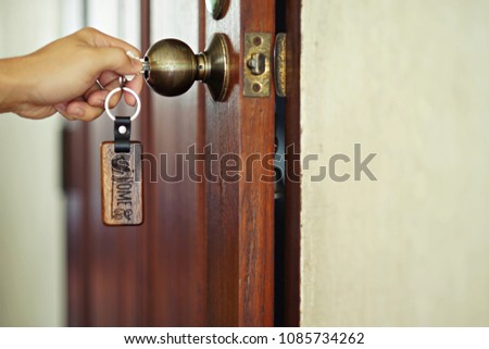 Photo of Hand using house key with wood home keyring to open front door, key and home concept