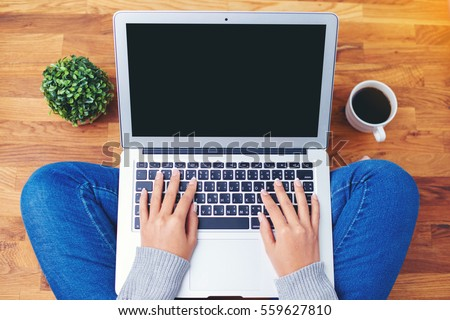 hand using laptop on wooden background #559627810