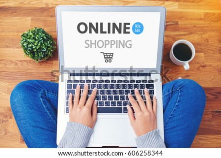 hand using laptop on wooden background, online shopping concept