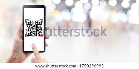 Hand using mobile smart phone scan Qr code on shopping mall banner background. Barcode reader, Qr code payment, Cashless technology, Digital money concept.