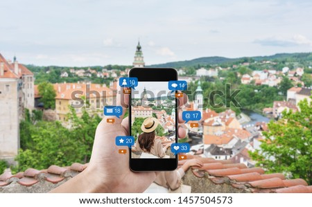 Hand using mobile smart phone taking photo of woman traveling in Cesky krumlov, Czech Republic, with social media and social network notification icons