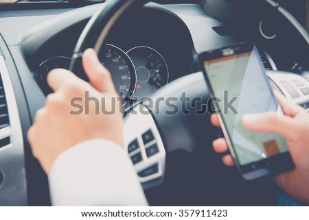 Hand using phone sending a text while driving to work ,businessman ,vintage color tone