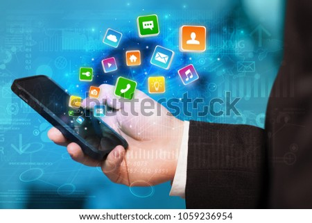 Hand using phone with bouncing colorful application and global reports and graphs concept