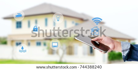 Hand using smart phone as smart home control application over blurred house background, banner, smart home concept #744388240