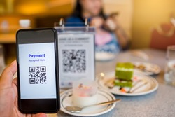 Hand using smart phone to scan QR code on tag with blurry food, dessert and customers in coffee shop to accepted generate digital pay without money. Qr code payment concept.
