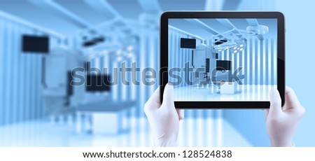 hand using tablet computer show equipment and medical devices in modern operating room