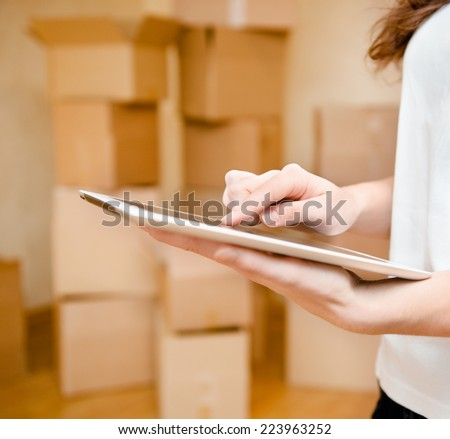 hand using tablet computer with cardboard boxes on background