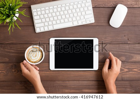 hand using white tablet blank screen on table workspace