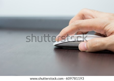 Hand using wireless mouse on wooden table #609781193