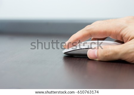 Hand using wireless mouse on wooden table #610763174
