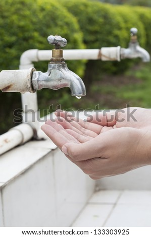 Hand wait for dripping water from old faucet