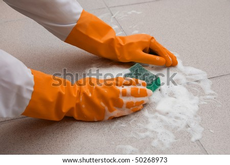 hand washing floor by cleaning sponge with foam