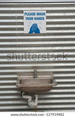 hand washing station mounted against corrugated iron