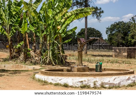 Hand water pump in Africa near banana trees #1198479574