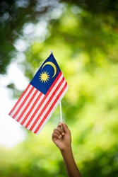 Hand waving flag of malaysia during independence day.