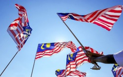 Hand waving Malaysia flag also known as Jalur Gemilang against the blue sky. People fly the flag in conjunction with the Independence Day celebration or Merdeka Day.