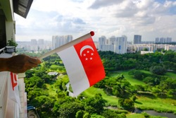 Hand waving Singapore flag outside apartment balcony corridor on bright sunny day. Lush green open space park, and skyline in the background; celebrate national day