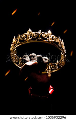 hand wearing coral beads clenching a gold crown raised up, with fire raining down from the sky with a black backdrop . Depicting a conquered kings crown after a war antebellum