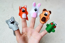 Hand wearing 5 finger puppets; wolf, fox, rabbit, bear, frog