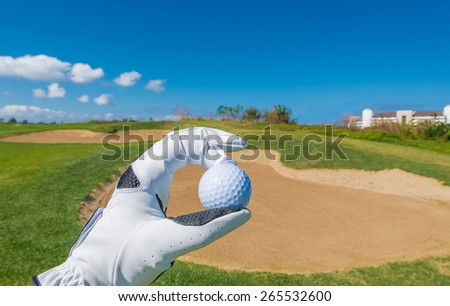 Hand wearing golf glove holding golf ball over beautiful course with blue sky.