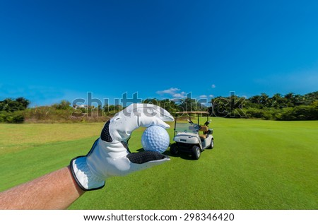 Hand wearing golf glove holding golf ball over beautiful course with blue sky. Vertical.