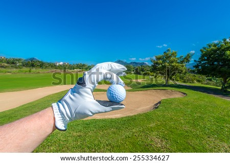 Hand wearing golf glove holding golf ball over beautiful golf course with blue sky.