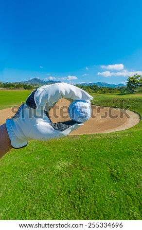 Hand wearing golf glove holding golf ball over beautiful golf course with blue sky.g