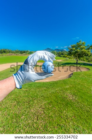 Hand wearing golf glove holding golf ball over beautiful golf course with blue sky. Vertical.