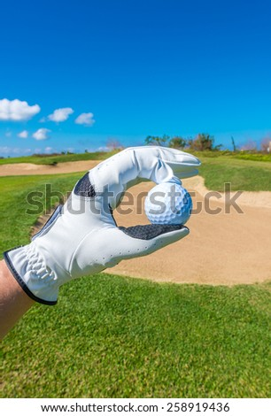 Hand wearing golf glove, holding golf ball over beautiful golf course with sand bunkers at the back. Vertical.