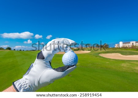 Hand wearing golf glove, holding golf ball over beautiful golf course with sand bunkers at the back.