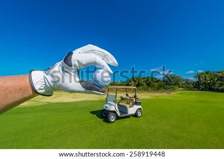 Hand wearing golf glove, holding golf ball over beautiful golf course with the golf cart at the back.