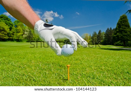 Hand wearing golf glove placing golf ball on the tee over beautiful golf course with blue sky