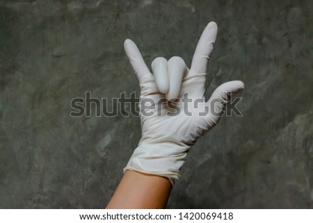 Hand wearing rubber gloves with ILY symbol. The ILY is a sign from the letters I, L and Y stand for I Love You. It is as a gesture created from a combination of the letters among deaf schoolchildren.