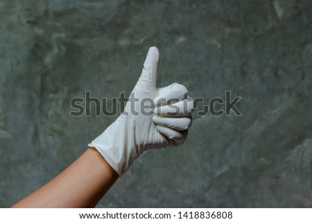 Hand wearing rubber gloves with thumbs up symbol. Thumbs up is used as a gesture. It's mean agreement, approval a great success. Gestures are a form of nonverbal communication in visible bodily action #1418836808