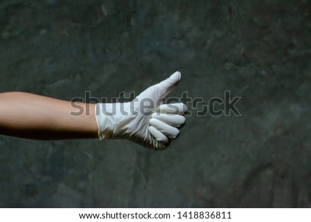 Hand wearing rubber gloves with thumbs up symbol. Thumbs up is used as a gesture. It's mean agreement, approval a great success. Gestures are a form of nonverbal communication in visible bodily action #1418836811