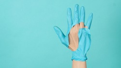 Hand Wearing torn medical gloves or torn rubber gloves on blue and green  or Tiffany Blue color background.monotone coclor.