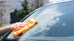 Hand wiping the windshield of a car on a sunny day. Wipe dry with an orange sponge. Rag wipes water stains on the window