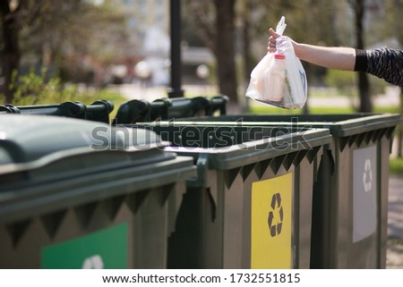 Hand with a bag of plastic garbage over containers for separation and sorting in Russia with the words: Glass, plastic, household waste. Waste sorting, the concept of eco-friendly garbage collection Foto stock ©