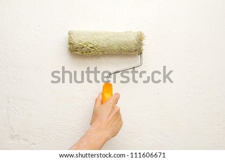 hand with a brush, paint the wall