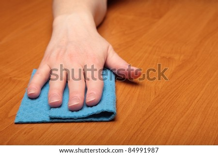 Hand with a cellulose sponge, table