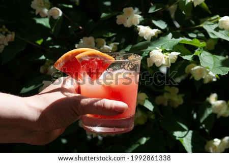 Hand with a glass of grapefruit juice