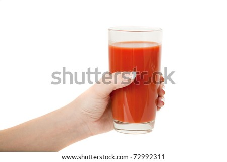 hand with a glass of tomato juice