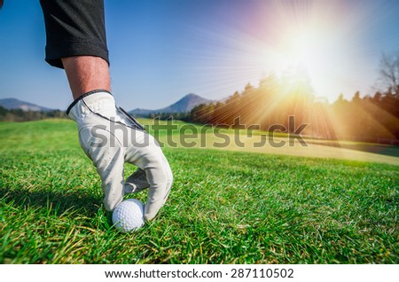 Hand with a glove is placing a t golf ball on the ground. Golf course with green grass with mountains in the background. Soft focus or shallow depth of field. Sunshine in the background