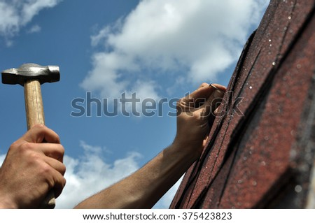 Hand with a hammer to drive a nail, roof repairs? Hand with a hammer to drive a nail, roof repairs. Bitumen Roof Asphalt Shingles.