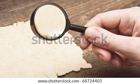 hand with a magnifier on old paper