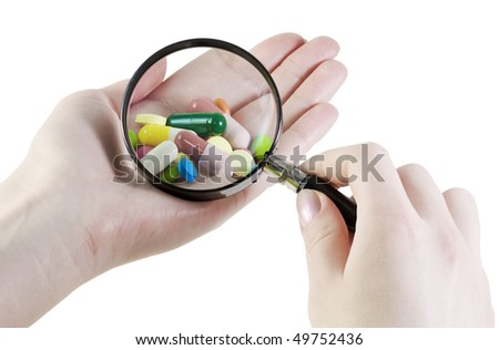hand with a magnifying glass looking at pills
