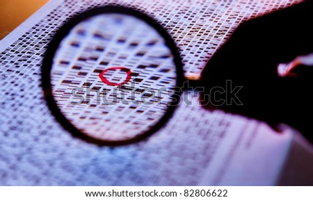 Hand with a magnifying glass on the banded DNA sequences - stock photo