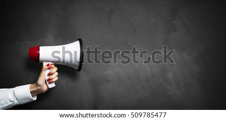 hand with a megaphone in front of an empty blackboard