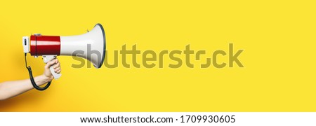 hand with a megaphone in front of an empty yellow background, banner size, with copyspace for your individual text.